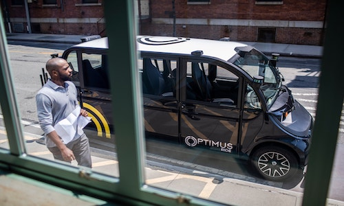 An Optimus car parked on a Brooklyn street.